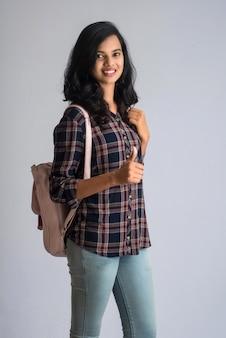 Молодая девушка показывает палец с рюкзаком