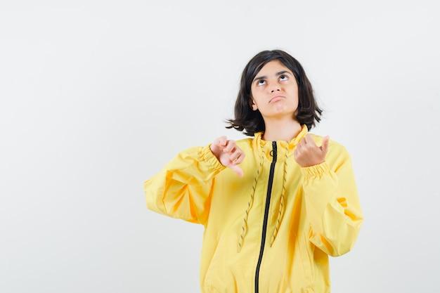 어린 소녀 아래로 엄지 손가락을 보이고 노란색 폭격기 재킷에 뭔가에 대해 생각하고 잠겨있는 찾고