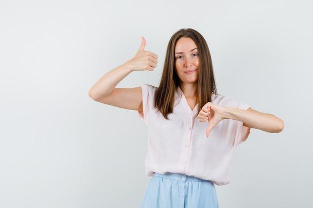 Tシャツ、スカートで親指を上下に見せて、賢明に見える、正面図の若い女の子。