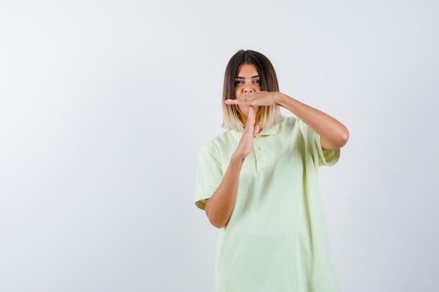 T- 셔츠에 시간 휴식 제스처를 표시 하 고 심각한 찾고 어린 소녀. 전면보기.