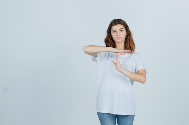 白いtシャツでタイムブレイクジェスチャーを示し、自信を持って、正面図を見て若い女の子。