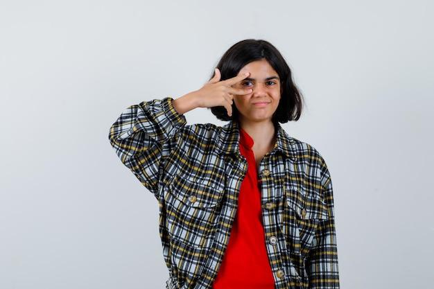 Giovane ragazza che mostra il segno v sull'occhio in camicia a quadri e maglietta rossa e sembra felice. vista frontale.