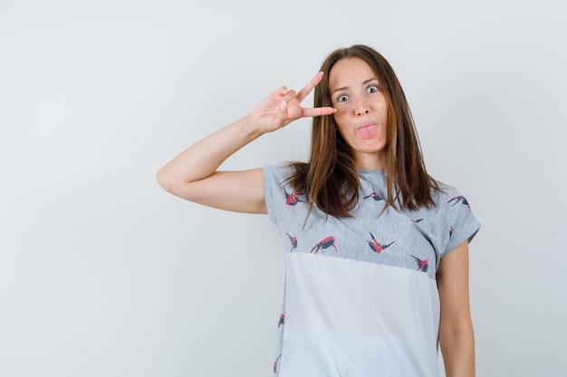Молодая девушка показывает v-знак возле глаза в футболке и выглядит сумасшедшей, вид спереди.