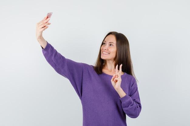 紫のシャツを着て自分撮りをしながら元気に見えるvサインを示す少女。正面図。