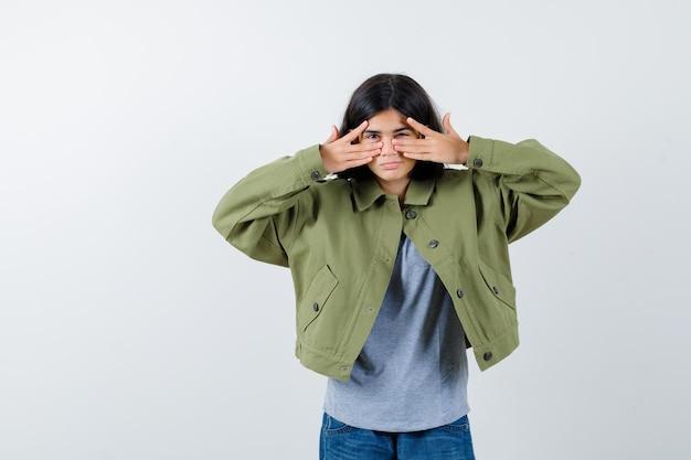 Giovane ragazza che mostra segni di v sull'occhio in maglione grigio, giacca color kaki, pantaloni di jeans e dall'aspetto serio. vista frontale.