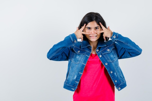 Giovane ragazza che mostra segni v sull'occhio in maglietta rossa e giacca di jeans e sembra carina. vista frontale.