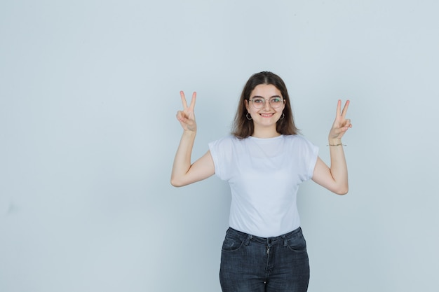 Молодая девушка показывает знак победы в футболке, джинсах и выглядит счастливым, вид спереди.