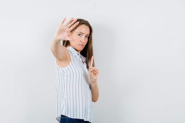 Young girl showing wait a minute gesture in t-shirt, jeans and looking serious. .