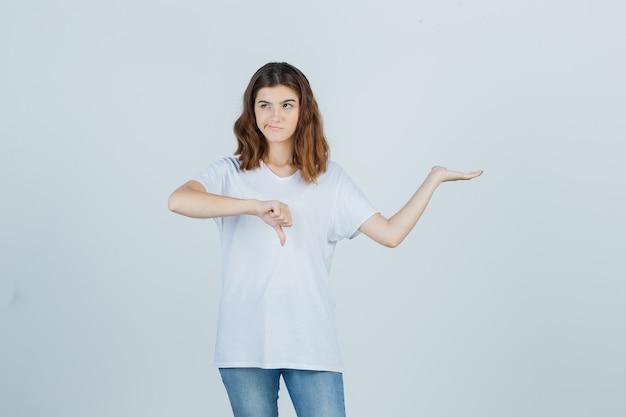 白いtシャツに親指を下に向けて歓迎のジェスチャーを示し、躊躇している若い女の子、正面図。