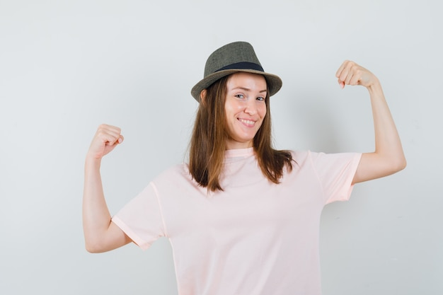 ピンクのtシャツ、帽子で勝者のジェスチャーを示し、陽気に見える少女。正面図。
