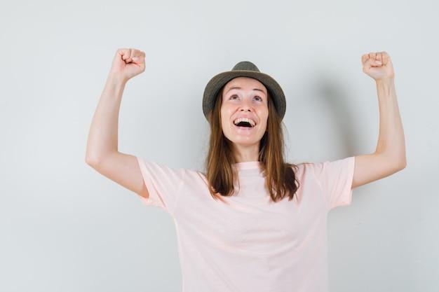 분홍색 티셔츠, 모자에 우승자 제스처를 보여주는 어린 소녀와 행복을 찾고. 전면보기.