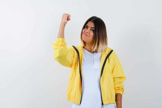 白いtシャツ、黄色のジャケットで勝者のジェスチャーを示し、幸運な顔をしている少女、正面図。