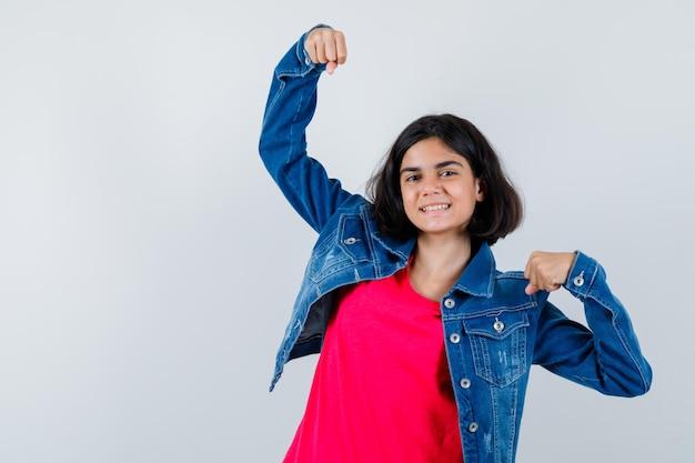 Giovane ragazza che mostra il gesto del vincitore in maglietta rossa e giacca di jeans e sembra felice.