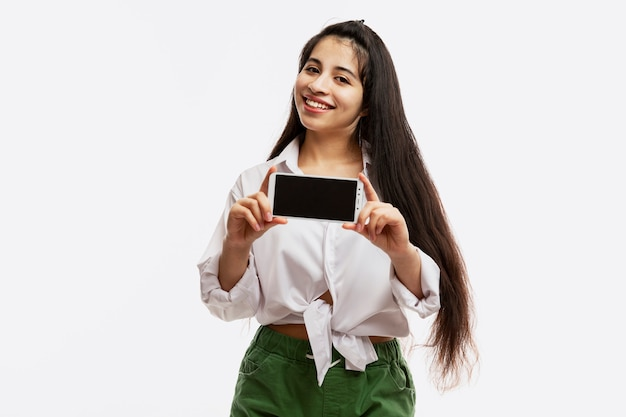 若い女の子は、空白の画面のスマートフォンを示しています。白いシャツと緑のショートパンツで長い髪の美しい明るいブルネット。