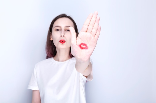 Young girl shows palm with kiss imprints red lipstick. world kissing day concept, air kiss.