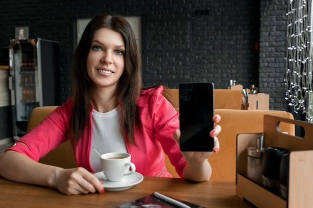 Young girl shows phone in camera sitting in cafe at table. a wooden table, a cup of coffee.