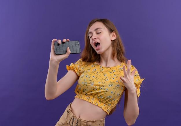 孤立した紫色の壁にマイクとして携帯電話を使用して歌う少女