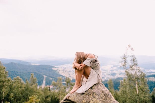 Молодая девушка сидит на камне на вершине горы и обнимает ее ноги с головой, лежа на коленях.
