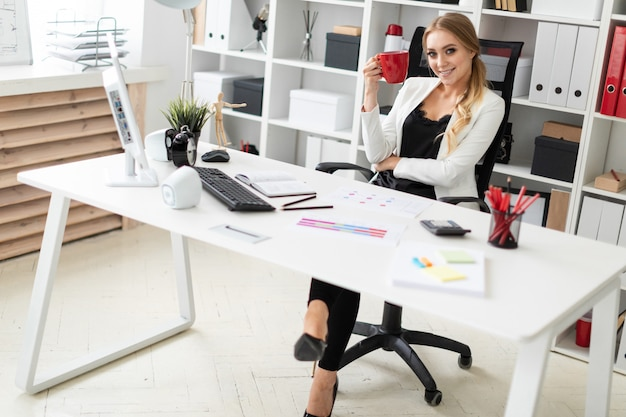 A young girl sits at a computer desk in the office and holds a red cup in her hand. before the girl on the table are diagrams.