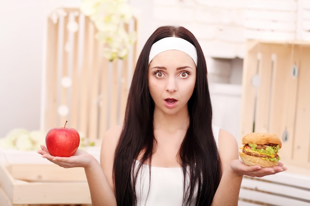 A young girl sits at home and makes a choice between healthy food and hamburger