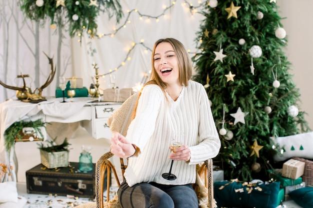어린 소녀는 크리스마스 트리 앞에서 안락의 자에 앉아