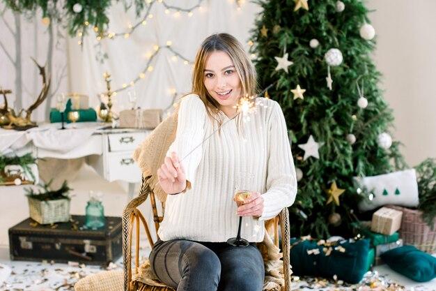 若い女の子はクリスマスツリーの前に肘掛け椅子に座っています