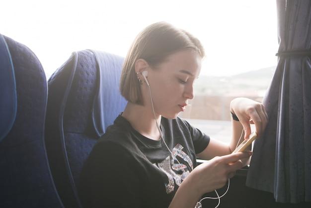 어린 소녀는 창에서 버스에 앉아 스마트 폰을 사용하고 헤드폰에서 음악을 듣습니다.
