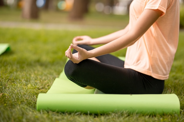 若い女の子は、暖かい日に公園の緑の芝生で他の女の子と一緒に運動をしている蓮華座に座っています。 。
