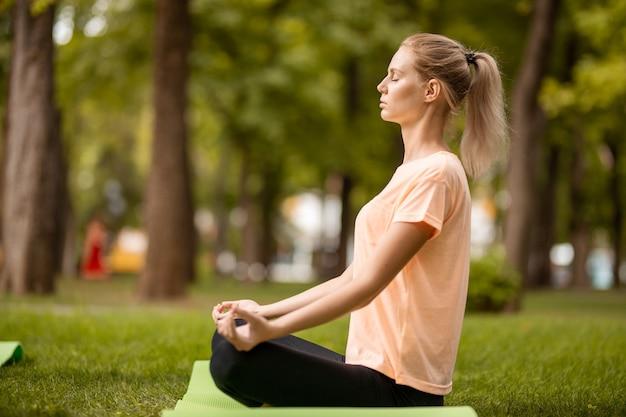 若い女の子は、暖かい日に公園の緑の芝生で他の女の子と運動をしている目を閉じて蓮華座に座っています。 。