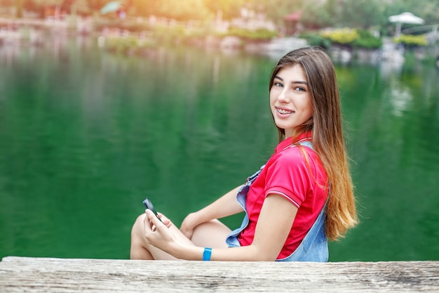 A young girl sits at the lake and communicates in social networks.