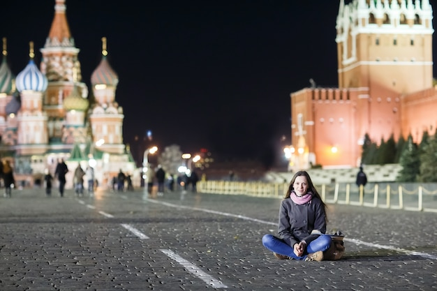 A young girl sits on red square in moscow