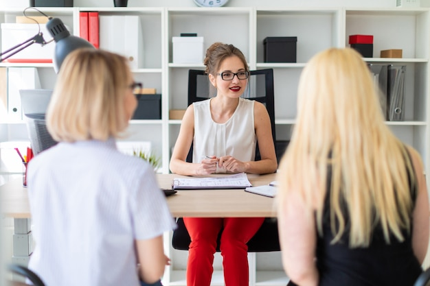 A young girl sits at a table in her office and talks to two co-partners.