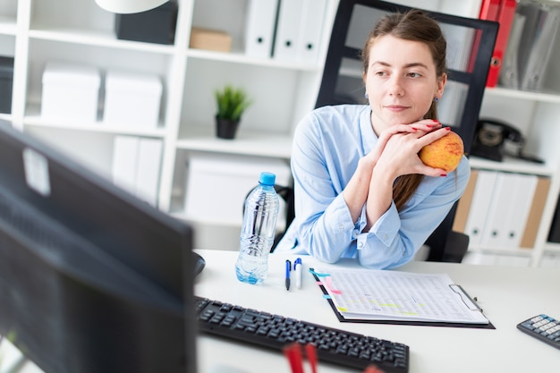 A young girl sits at a table in the office and holds an apple in her hand.