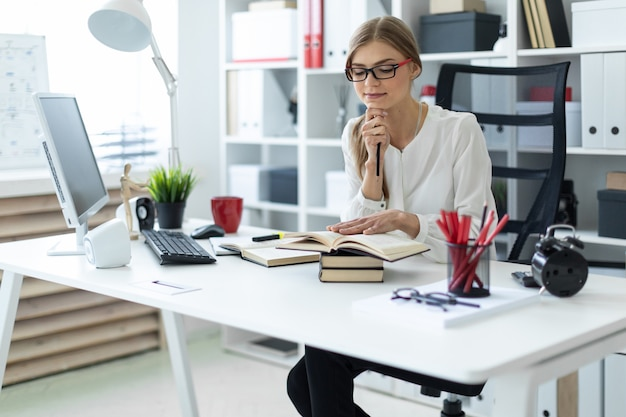 A young girl sits at a table in the office and holds a pencil in her hand. before the girl lies an open book.