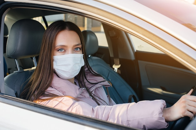 A young girl sits behind the wheel in the car in the mask during the global pandemic and coronavirus. quarantine.