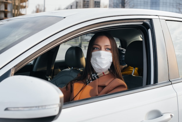 Young girl sits behind the wheel in the car in the mask during the global pandemic and coronavirus.
