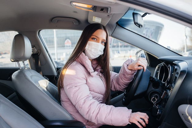 Young girl sits behind the wheel in the car in the mask during the global pandemic and coronavirus