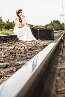 A young girl sits with a suitcase on the railway tracks.