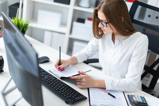 어린 소녀는 테이블에 앉아 컴퓨터, 문서 및 계산기 작업