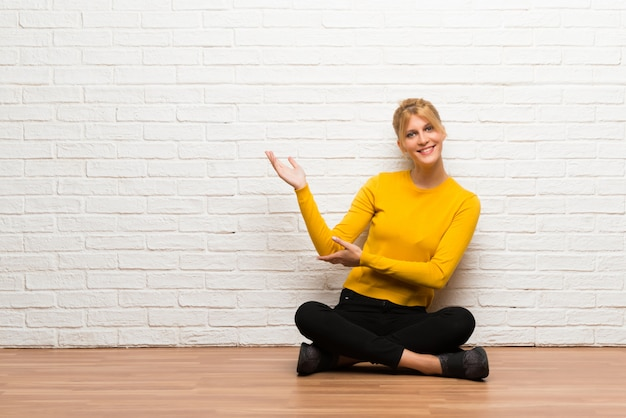 Young girl sitting on the floor extending hands to the side for inviting to come