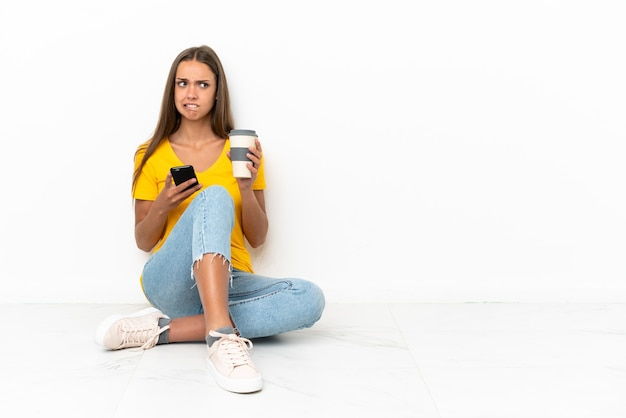 Young girl sitting on the floor holding coffee to take away
