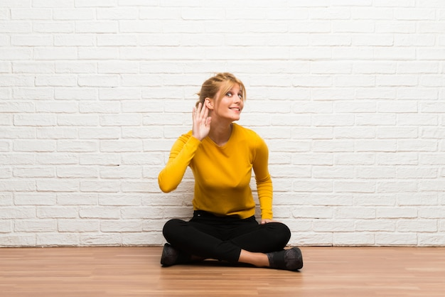 Young girl sitting on the floor listening to something by putting hand on the ear