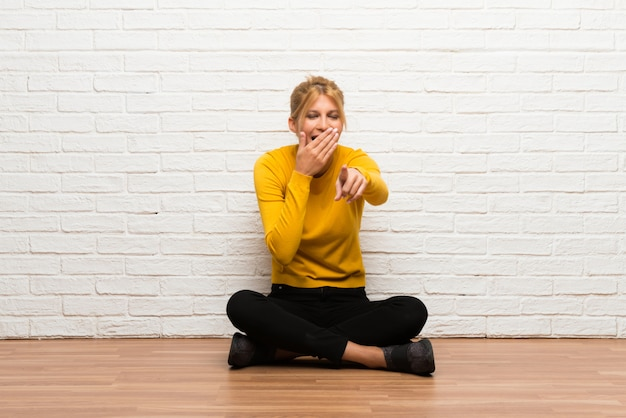Young girl sitting on the floor pointing with finger at someone and laughing