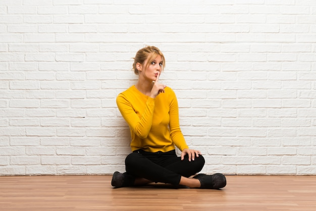 Young girl sitting on the floor showing a sign of closing mouth and silence gesture