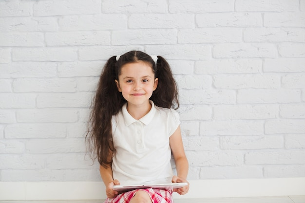 Young girl sitting on floor smiling
