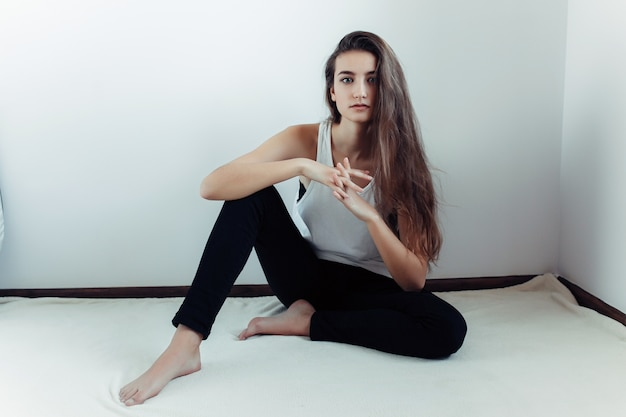 Young girl sitting on the floor with fingers crisscrossed