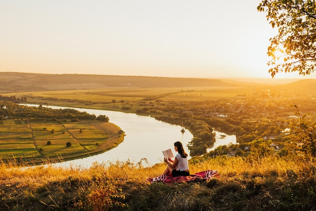 Young girl sitting on a hill with beautiful landscape and reading book. sunset.