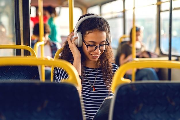 어린 소녀는 버스에 앉아 음악을 듣고.