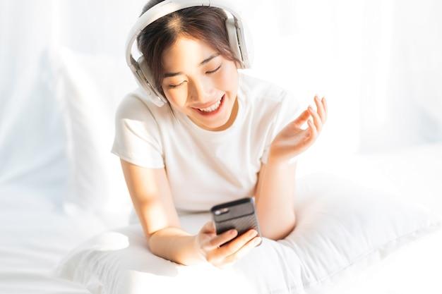 面白い音楽を聴いてベッドに座っている若い女の子