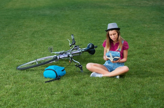 Young girl sitting near bycicle on grass.